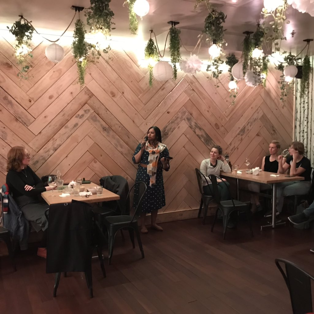 Image of Upulie speaking with a wider view of the Arborist. There are table, with people sitting at them, and light and greenery hanging from the ceiling.