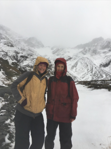Rebecca and Rhian are dressed in big coats and are standing in front of large snow mountains.